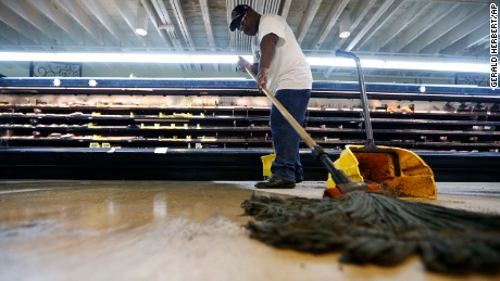 Randy Davis, manager at the Circle Food Store, mops the floor after the store flooded during Saturday's torrential rains in New Orleans