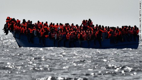 TOPSHOT - Migrants wait to be rescued as they drift in the Mediterranean Sea some 20 nautical miles north off the coast of Libya on October 3, 2016. 