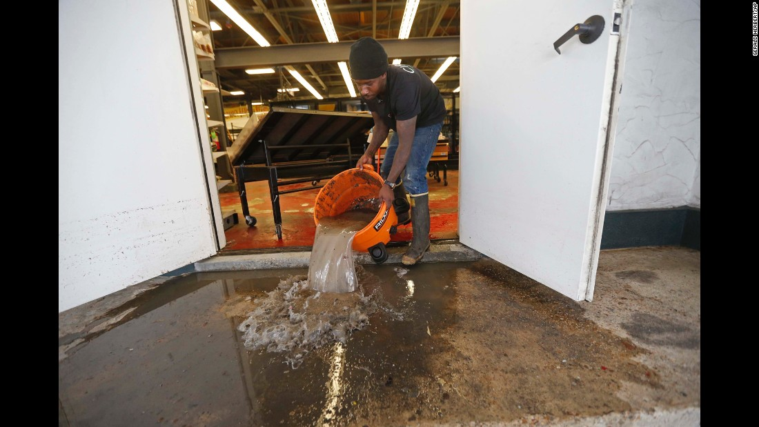 "Dwayne Boudreaux Jr., owner of the Circle Food Store in New Orleans, dumps out dirty floodwater on Monday, August 7. A historic rainstorm<a href=""http://www.cnn.com/2017/08/09/us/new-orleans-flood-fallout/index.html"" target=""_blank""> flooded homes and exposed critical weaknesses</a> in the city's drainage pumping operation."