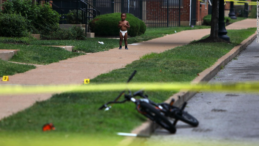 A baby stands outside a home in St. Louis as police investigate the scene of a fatal shooting on Monday, August 7.