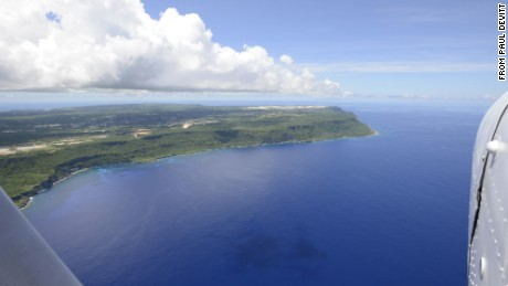Guam's green flora and Andersen Air Force base can be seen from above.