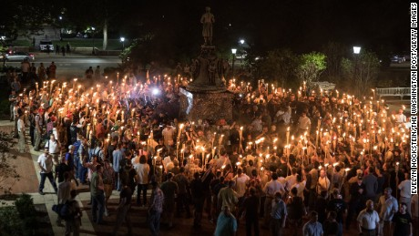 "White nationalists carrying torches surround a group of protesters around a statue of Thomas Jefferson on the University of Virginia's campus Friday night. Scuffles broke out between the groups. Earlier, the white nationalists were chanting ""White lives matter"" and ""You will not replace us!"" as they marched on campus."