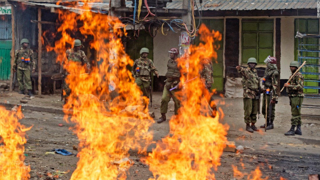 Riot police prepare to pass burning barricades as they push toward protesters during clashes on August 12, 2017, in the Mathare slum of Nairobi, Kenya. Demonstrators objected to the re-election of President Uhuru Kenyatta over opposition leader and former Prime Minister Raila Odinga.