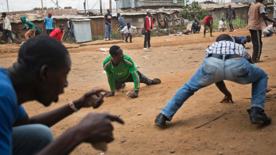 Odinga supporters duck for cover as they face off against Kenyan security forces in the Kibera slum of Nairobi.