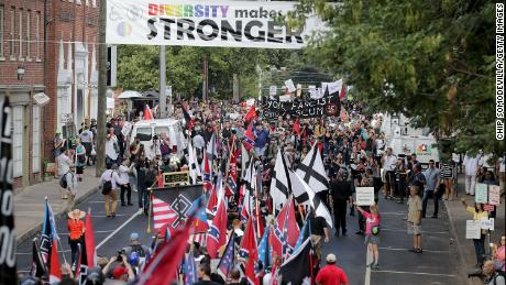 "Hundreds of white nationalists, neo-Nazis and members of the ""alt-right"" march down East Market Street toward Lee Park during the ""United the Right"" rally August 12 in Charlottesville, Virginia. After clashes with anti-facist protesters and police the rally was declared an unlawful gathering and people were forced out of Lee Park, where a statue of Confederate General Robert E. Lee is slated to be removed."