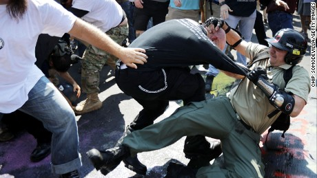 "White nationalists, neo-Nazis and members of the ""alt-right"" clash with counter-protesters as they enter Lee Park during the ""Unite the Right"" rally August 12, 2017 in Charlottesville, Virginia. After clashes with anti-fascist protesters and police the rally was declared an unlawful gathering and people were forced out of Lee Park, where a statue of Confederate General Robert E. Lee is slated to be removed."