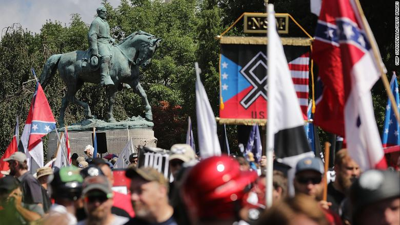 "A statue of Confederate General Robert E. Lee stands behind a crowd of white nationalists, neo-Nazis and members of the ""alt-right"" movement during the ""Unite the Right"" rally on August 12, 2017 in Charlottesville, Virginia. After clashes with counterprotesters and police, the rally was declared an unlawful gathering and protesters were forced out of Lee Park, where the statue is slated to be removed."