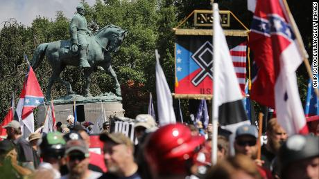"The statue of Confederate General Robert E. Lee stands behind a crowd of hundreds of white nationalists, neo-Nazis and members of the ""alt-right"" during the ""Unite the Right"" rally August 12, 2017 in Charlottesville, Virginia. After clashes with anti-fascist protesters and police the rally was declared an unlawful gathering and people were forced out of Lee Park, where a statue of Confederate General Robert E. Lee is slated to be removed."