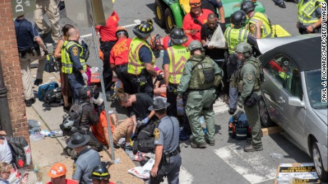People receive first-aid after a car accident ran into a crowd of protesters in Charlottesville, Virginia on August 12, 2017.