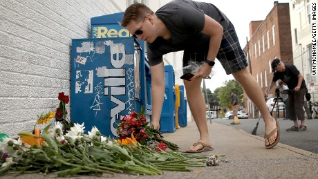 A man places flowers at a makeshift memorial for the victims of Saturday's attack, in which a car plowed into a crowd of demonstrators opposing a nearby white nationalist rally in Charlottesville, Virginia.