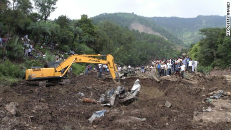 Heavy machinery removes debris as rescue personnel search for survivors and bodies of victims after a landslide along a highway in Northern India.