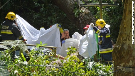 Firefighters work at the area where a tree fell down killing 11 people in Funchal on August 15, 2017. At least 11 people were crushed to death today when a 200-year-old oak tree fell at a religious festival on the Portuguese island of Madeira, local media reported. / AFP PHOTO / Helder SANTOS        (Photo credit should read HELDER SANTOS/AFP/Getty Images)