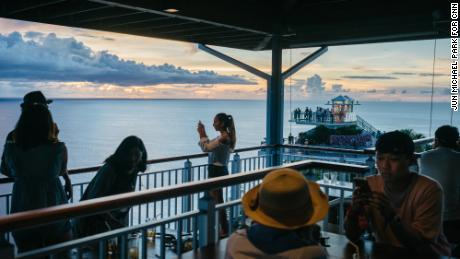Tourists take pictures of sunset at Terraza Cafe and Grill in Two Lovers Point, Guam. Aug 14, 2017.
