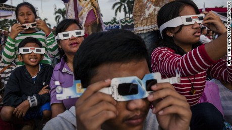 PALEMBANG, SUMATRA, INDONESIA - MARCH 09:  People gather as watch  the total solar eclipse in Palembang city on March 9, 2016 in Palembang, South Sumatra province, Indonesia. A total solar eclipse swept across Indonesia on Wednesday, seen by sky gazers and marked by parties, colourful tribal rituals and Muslim prayers.  (Photo by Ulet Ifansasti/Getty Images)