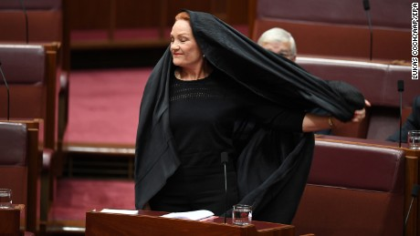 epaselect epa06147929 One Nation Leader Senator Pauline Hanson takes off a full Islamic burqa veil during Senate Question Time at Parliament House in Canberra, Australian Capital Territory, Australia, 17 August 2017. Hanson attended Senate Question Time wearing a full burqa and she is expected to deliver later in the day a speech calling for the banning on full face coverings in public, media reported. Her identity was checked before entering the red chamber, media added.  EPA/LUKAS COCH  AUSTRALIA AND NEW ZEALAND OUT