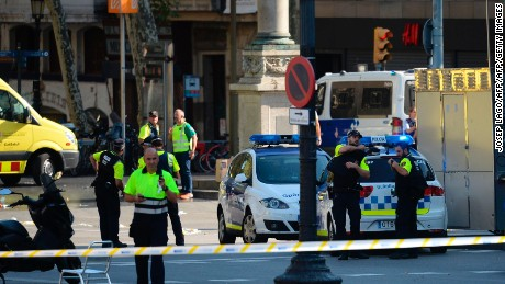 "Medical staff members and policemen stand in a cordoned off area after a van ploughed into the crowd, injuring several persons on the Rambla in Barcelona on August 17, 2017. Police in Barcelona said they were dealing with a ""terrorist attack"" after a vehicle ploughed into a crowd of pedestrians on the city's famous Las Ramblas boulevard on August 17, 2017. Police were clearing the area after the incident, which has left a number of people injured. / AFP PHOTO / Josep LAGO        (Photo credit should read JOSEP LAGO/AFP/Getty Images)"