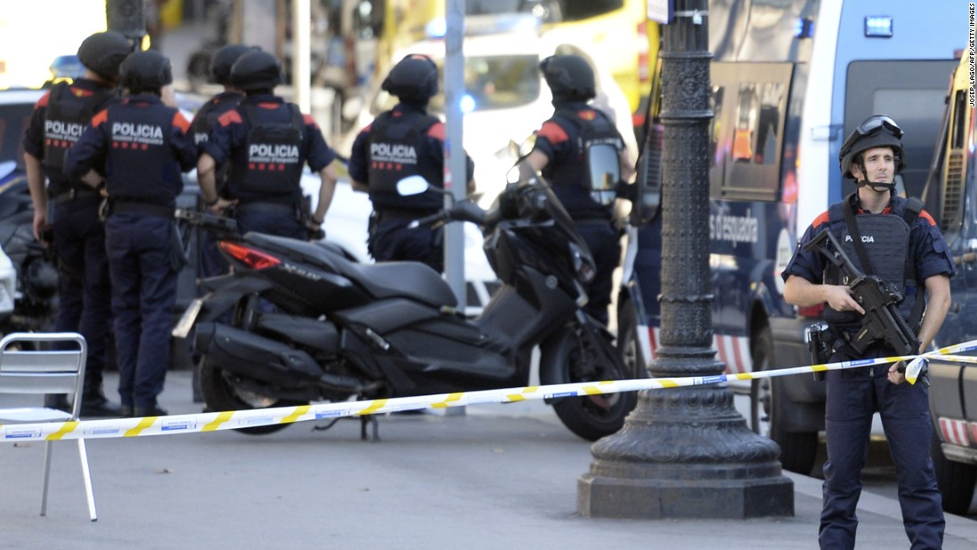 Armed police officers stand in a cordoned-off area. One person has been arrested, Catalan police said.