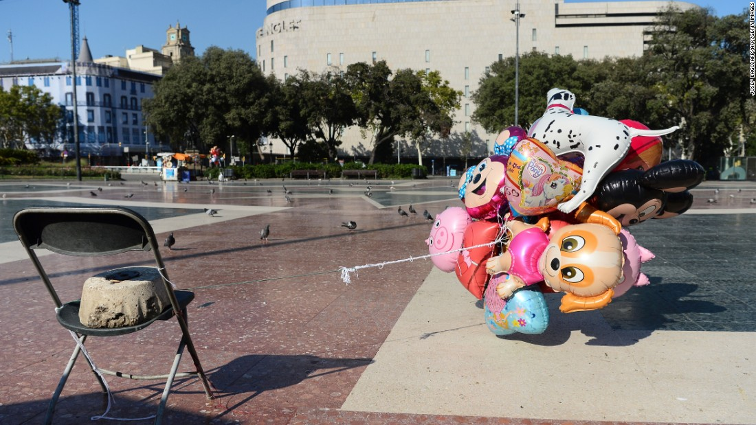 A street vendor's abandoned air balloons are tied to a chair in the empty Plaça de Catalunya.