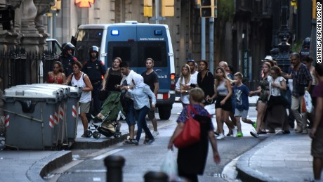 People flee the scene in Barcelona, Spain, Thursday, Aug. 17, 2017, as police officers patrols after a white van jumped the sidewalk in the historic Las Ramblas district, crashing into a summer crowd of residents and tourists and injuring several people, police said. (AP Photo/Giannis Papanikos)