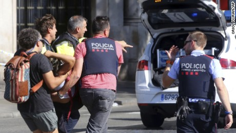 An injured person is carried in Barcelona on Thursday.