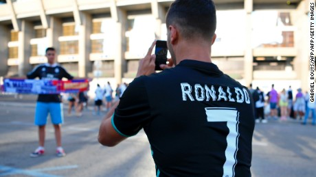 A fan wearing a Ronaldo's jersey takes a picture prior to the Spanish Supercup football match Real Madrid vs FC Barcelona outside the Santiago Bernabeu stadium in Madrid, on August 16, 2017. / AFP PHOTO / GABRIEL BOUYS        (Photo credit should read GABRIEL BOUYS/AFP/Getty Images)