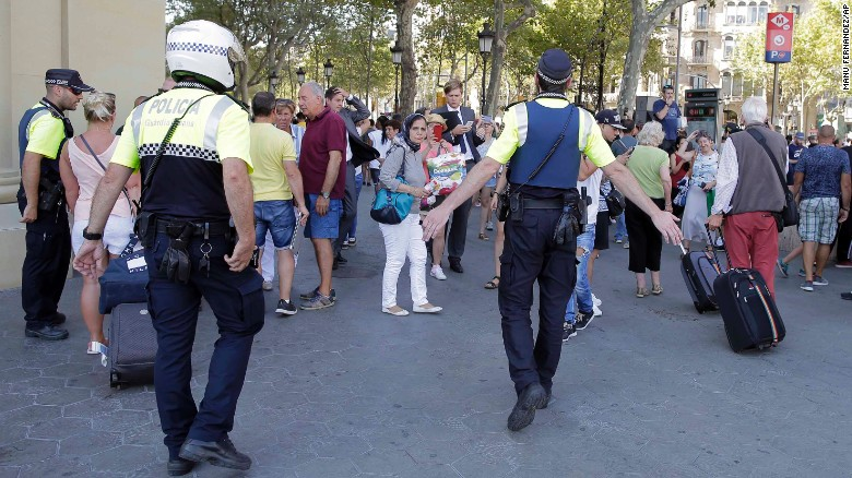 Police officers tell members of the public to leave the scene in Barcelona on Thursday.