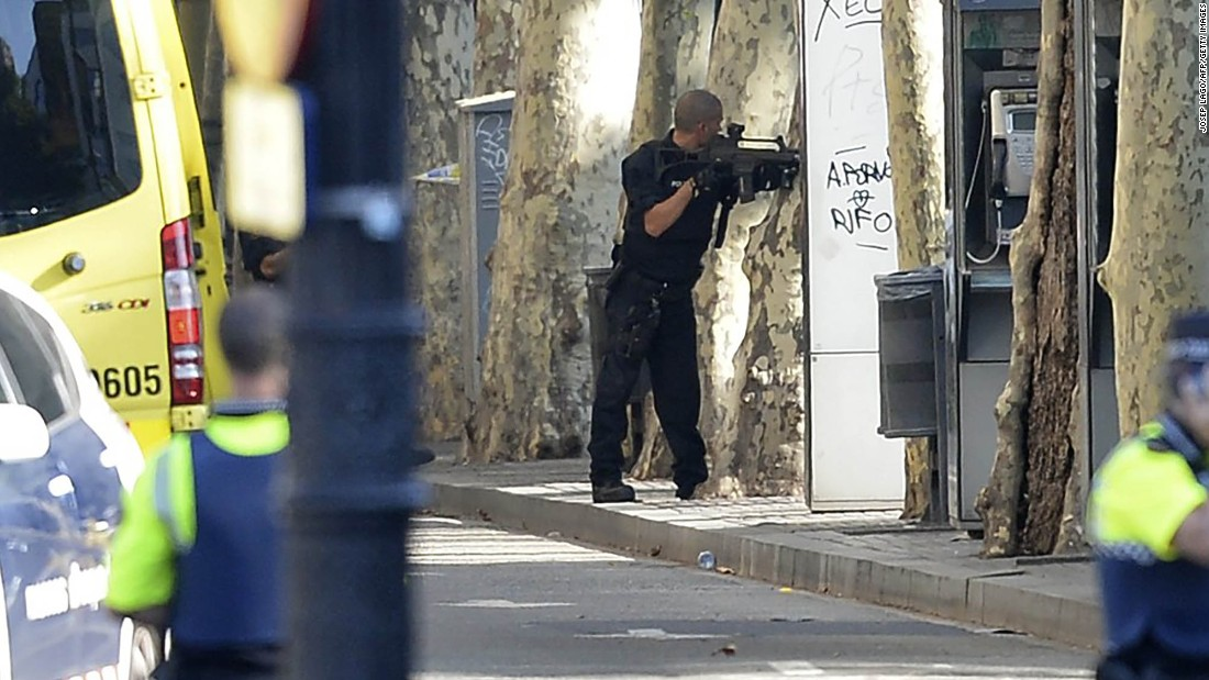 A police officer stands behind a tree in the cordoned-off area.