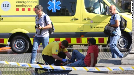 An injured person is treated Thursday after a van jumped the sidewalk in Barcelona's Las Ramblas area.