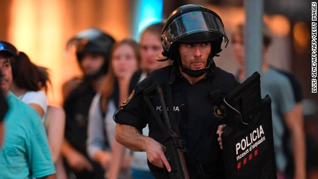 "Spanish policemen stand guard in a cordoned off area after a van ploughed into the crowd, killing 13 persons and injuring over 50 on the Rambla in Barcelona on August 17, 2017. A driver deliberately rammed a van into a crowd on Barcelona's most popular street on August 17, 2017 killing at least 13 people before fleeing to a nearby bar, police said.  Officers in Spain's second-largest city said the ramming on Las Ramblas was a ""terrorist attack"" and a police source said one suspect had left the scene and was ""holed up in a bar"". The police source said they were hunting for a total of two suspects. / AFP PHOTO / LLUIS GENE        (Photo credit should read LLUIS GENE/AFP/Getty Images)"