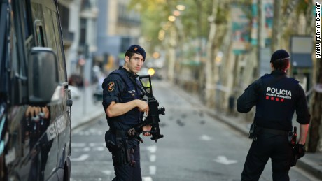 Armed police officers patrol a deserted street in Las Ramblas, in Barcelona, Spain, Friday, Aug. 18, 2017. A white van jumped up onto a sidewalk and sped down a pedestrian zone Thursday in Barcelona's historic Las Ramblas district, swerving from side to side as it plowed into tourists and residents. Police said 13 people were killed and more than 50 wounded in what they called a terror attack.(AP Photo/Manu Fernandez)