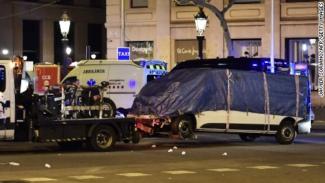 "The van that ploughed into the crowd, killing at least 13 people and injuring around 100 others is towed away from the Rambla in Barcelona on August 18, 2017. A driver deliberately rammed a van into a crowd on Barcelona's most popular street on August 17, 2017 killing at least 13 people before fleeing to a nearby bar, police said. Officers in Spain's second-largest city said the ramming on Las Ramblas was a ""terrorist attack""."
