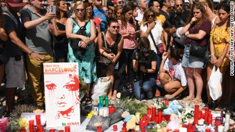 People stand next to flowers, candles, a poster reading 'Pray for Barcelona' and other items set up on the Las Ramblas boulevard in Barcelona as they pay tribute to the victims of the Barcelona attack, a day after a van ploughed into the crowd, killing 13 persons and injuring over 100 on August 18, 2017. Police hunted for the driver who rammed a van into pedestrians on an avenue crowded with tourists in Barcelona, leaving 13 people dead and  more than 100 injured, just hours before a second assault in a resort along the coast. / AFP PHOTO / PASCAL GUYOT        (Photo credit should read PASCAL GUYOT/AFP/Getty Images)