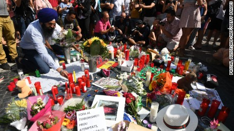People stand next to flowers, candles and other items set up on the Las Ramblas boulevard in Barcelona as they pay tribute to the victims of the Barcelona attack, a day after a van ploughed into the crowd, killing 13 persons and injuring over 100 on August 18, 2017.