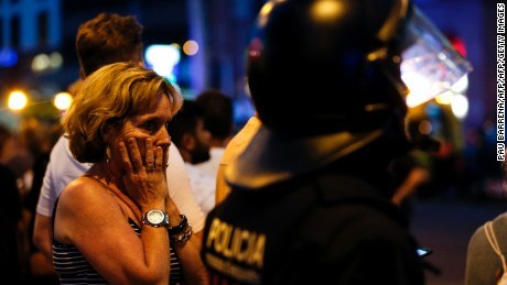 "TOPSHOT - A woman gestures as she is escorted out by Spanish policemen outside a cordoned off area after a van ploughed into the crowd, killing 13 persons and injuring over 80 on the Rambla in Barcelona on August 17, 2017. A driver deliberately rammed a van into a crowd on Barcelona's most popular street on August 17, 2017 killing at least 13 people before fleeing to a nearby bar, police said.  Officers in Spain's second-largest city said the ramming on Las Ramblas was a ""terrorist attack"". / AFP PHOTO / PAU BARRENA        (Photo credit should read PAU BARRENA/AFP/Getty Images)"