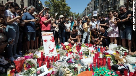People gather around tributes laid on Las Ramblas near the scene of yesterday's terrorist attack, on August 18, 2017 in Barcelona, Spain. Fourteen people were killed and dozens injured when a van hit crowds in the Las Ramblas area of Barcelona on Thursday. Spanish police have also killed five suspected terrorists in the town of Cambrils to stop a second terrorist attack.
