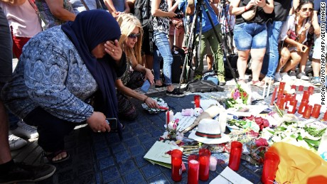 People gather next to flowers, candles and other items set up on the Las Ramblas boulevard in Barcelona as they pay tribute to the victims of the Barcelona attack, a day after a van ploughed into the crowd, killing 13 persons and injuring over 100 on August 18, 2017. Police hunted for the driver who rammed a van into pedestrians on an avenue crowded with tourists in Barcelona, leaving 13 people dead and  more than 100 injured, just hours before a second assault in a resort along the coast. / AFP PHOTO / PASCAL GUYOT        (Photo credit should read PASCAL GUYOT/AFP/Getty Images)