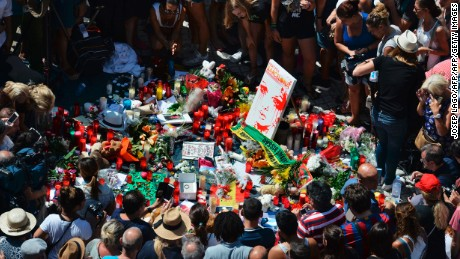 People gather to leave candles, flowers, messages, stuffed toys and many differents objects for the victims on August 18, 2017 at the spot where yesterday a van ploughed into the crowd, killing 14 persons and injuring over 100 on the Rambla boulevard in Barcelona. Drivers have ploughed on August 17, 2017 into pedestrians in two quick-succession, separate attacks in Barcelona and another popular Spanish seaside city, leaving 14 people dead and injuring more than 100 others. In the first incident, which was claimed by the Islamic State group, a white van sped into a street packed full of tourists in central Barcelona on Thursday afternoon, knocking people out of the way and killing 13 in a scene of chaos and horror. Some eight hours later in Cambrils, a city 120 kilometres south of Barcelona, an Audi A3 car rammed into pedestrians, injuring six civilians -- one of them critical -- and a police officer, authorities said. / AFP PHOTO / Josep LAGO        (Photo credit should read JOSEP LAGO/AFP/Getty Images)