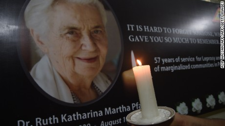 A Pakistani man holds a candle in front of a picture of German nun Ruth Pfau at the Marie Adelaide Leprosy Centre in Karachi on August 10, 2017.