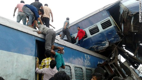 Railway police and volunteers look for survivors Saturday in wreckage of train derailment in northern Indian.
