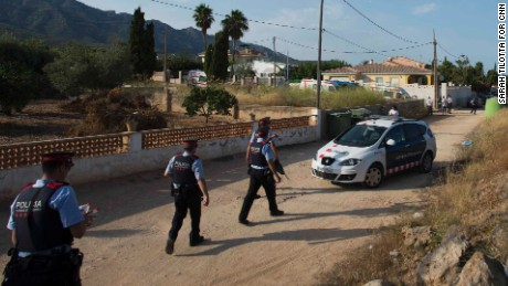 Armed police walk down a dirt road toward the scene of the explosion in Alcanar.