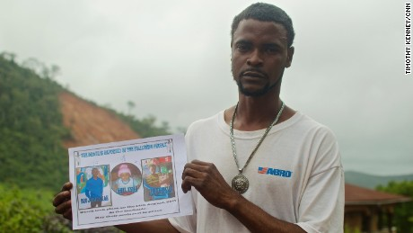 Gabriel Fattah Manga holds a poster showing the family members he lost in the mudslide that hit Sierra Leone's capital, Freetown.