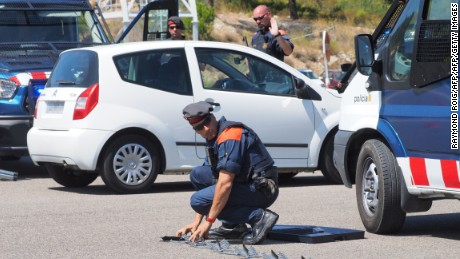 "A Spanish police officer deploys a ""spike strip"" at the border between La-Jonquera in northern Spain and Le-Perthus in southern France."