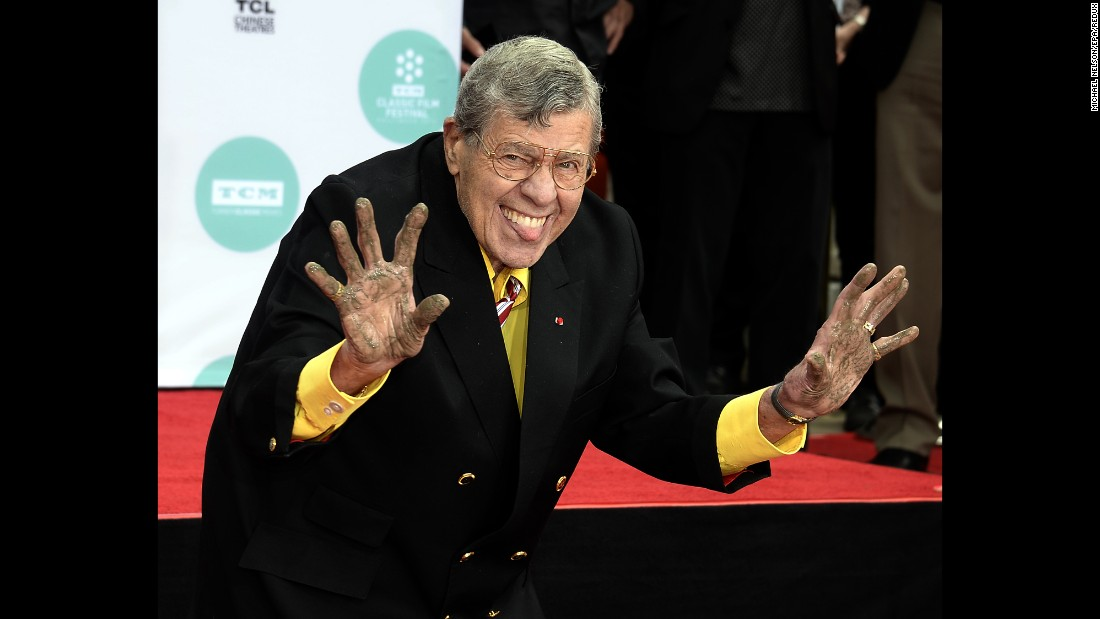 Lewis holds up his cement covered hands during a 2014 ceremony to add his hand prints and footprints to the sidewalk at the TCL Chinese Theatre in Hollywood.