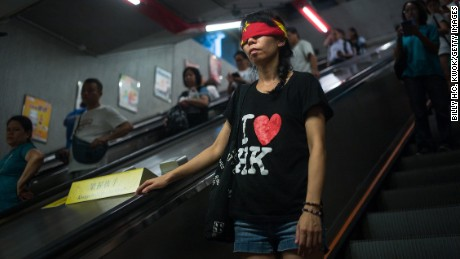 A protester covers her eyes with a China flag to imply Goddess of Justice during the rally supporting Wong, Law and Chow in Hong Kong's Central district Sunday.