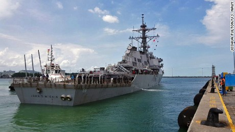 The guided-missile destroyer USS John S. McCain arrives pier side at Changi Naval Base, Republic of Singapore following a collision with the merchant vessel Alnic MC while underway east of the Straits of Malacca and Singapore. Significant damage to the hull resulted in flooding to nearby compartments, including crew berthing, machinery, and communications rooms. Damage control efforts by the crew halted further flooding. The incident will be investigated.