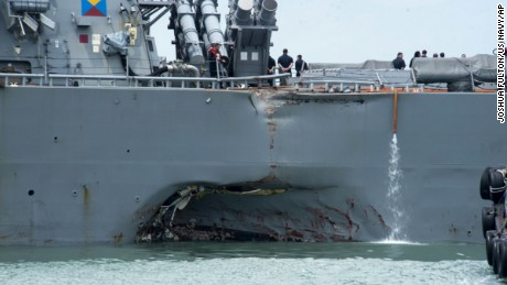 "Damage to the portside is visible as the Guided-missile destroyer USS John S. McCain (DDG 56) steers towards Changi naval base in Singapore following a collision with the merchant vessel Alnic MC Monday, Aug. 21, 2017. The USS John S. McCain was docked at Singapore's naval base with ""significant damage"" to its hull after an early morning collision with the Alnic MC as vessels from several nations searched Monday for missing U.S. sailors."