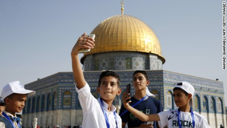 Palestinian children from the Gaza Strip pose for a picture near the Dome of the Rock mosque in the Al-Aqsa mosque compound in Jerusalem's old city on August 20, 2017 as they visit the city for the first time as part of an exchange program run by the UN agency for Palestinian refugees. Ninety-one children between the ages of eight and 14 crossed from the blockaded Palestinian enclave into Israel before visiting Jerusalem, according to United Nations agency for Palestinian refugees UNRWA. All but seven had never been out of the Gaza Strip.