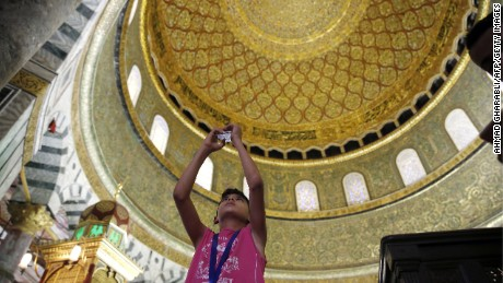 A Palestinian boy from Gaza takes a photo inside the Dome of the Rock mosque.