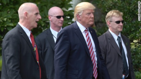 President Donald Trump, his longtime bodyguard Keith Schiller, left, and two Secret Service agents walk along the South Lawn of the White House in Washington, Monday, June 12, 2017, following a ceremony where the president honored the 2016 NCAA Football National Champions Clemson University Tigers.