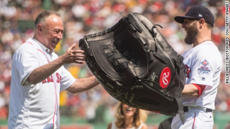 BOSTON, MA - AUGUST 20: Dustin Pedroia #15 of the Boston Red Sox presents NESN broadcaster Jerry Remy with a giant glove as a gift during a 30 year recognition ceremony before a game between the Boston Red Sox and the New York Yankees on August 20, 2017 at Fenway Park in Boston, Massachusetts. (Photo by Billie Weiss/Boston Red Sox/Getty Images)